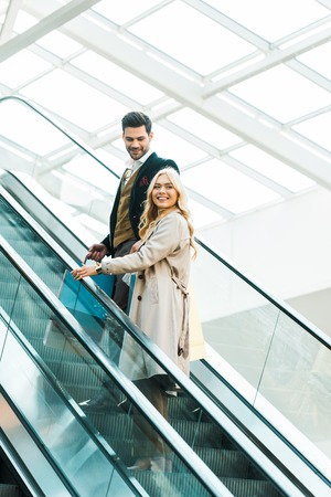 Happy elegant couple standing on escalator