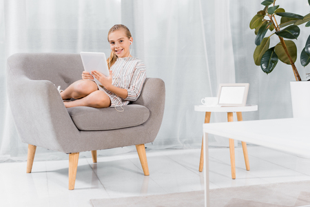 cheerful little child in earphones sitting on armchair with digital tablet at home Foto de archivo