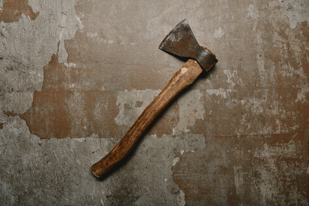 Top view of vintage rusty axe on old surface