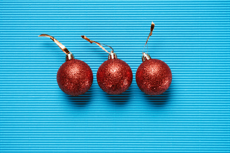 Flat lay of three red shiny decorative christmas balls on blue textured background