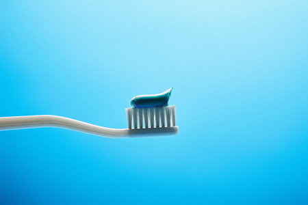 close up view of toothbrush with paste on blue backdrop 写真素材