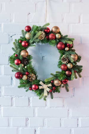 Christmas wreath hanging on white brick wall