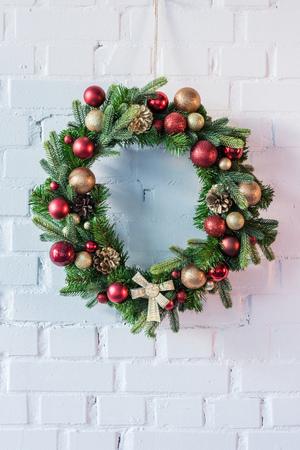 Corona de Navidad colgada en la pared de ladrillo blanco. Foto de archivo