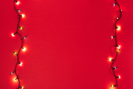 Two glowing garlands on red background with copy space