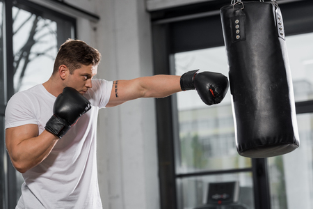 side view of handsome muscular boxer exercising with punching bag in gym