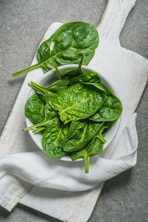 Top view of spinach leaves in bowl on white cutting board