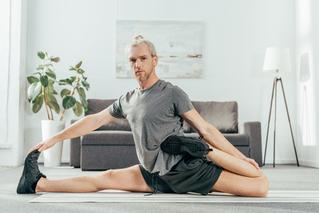 handsome adult man stretching on yoga mat and looking at camera while exercising at home Stockfoto