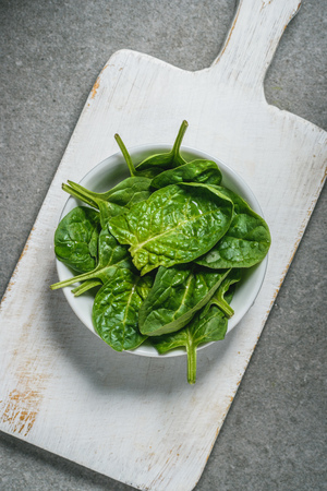 Top veiw of fresh picked spinach leaves in bowl on white cutting board