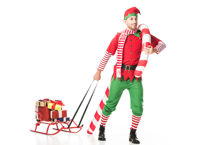 happy man in christmas elf costume carrying sleigh with presents and big candy cane isolated on white 版權商用圖片