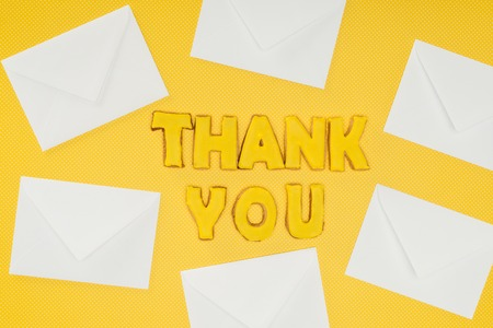thank you lettering in cookies with white envelopes isolated on yellow background 写真素材