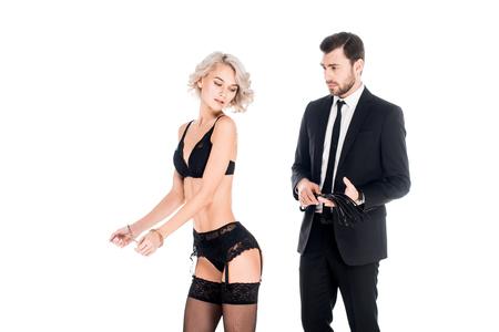 Merveilleuse femme debout en lingerie et menottes tandis que l'homme tenant un fouet isolé sur blanc Banque d'images