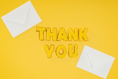 thank you lettering in cookies with white envelopes isolated on yellow background Stockfoto