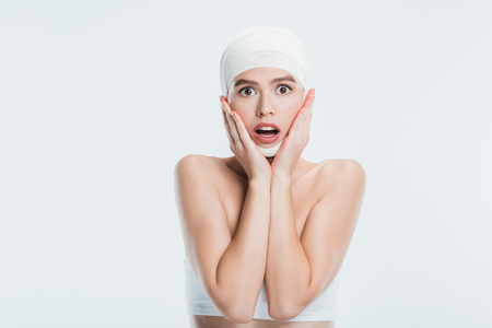 scared woman with bandages over head after plastic surgery isolated on white Imagens