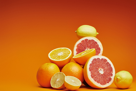 close-up view of fresh ripe whole and sliced citrus fruits on orange background