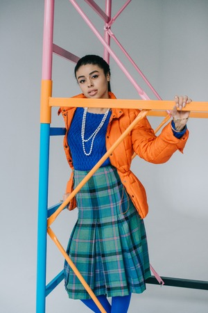 african american girl in orange winter jacket and checkered skirt posing near colorful scaffold in studio Imagens