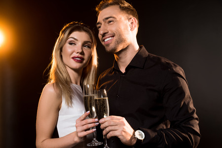 happy young couple with glasses of champagne standing together on black