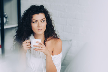 selective focus of curly woman drinking coffee in bed during morning time at home