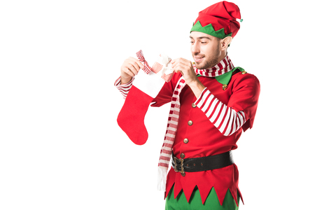 man in christmas elf costume putting present in red christmas stocking isolated on white Stock Photo