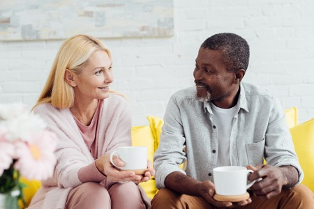 smiling mature woman sitting on sofa with african american man and drinking coffee together