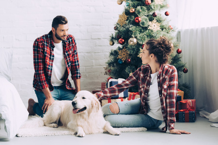 side view of beautiful girl petting dog and talking to boyfriend near christmas tree at home