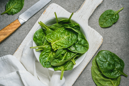 Top view of green spinach leaves in bowl on white cutting board