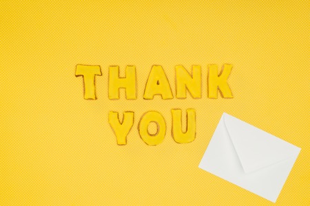 thank you lettering in cookies with blank white envelope isolated on yellow background