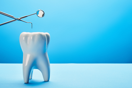 close up view of tooth model, dental mirror and probe on blue backdrop Banque d'images - 112159092