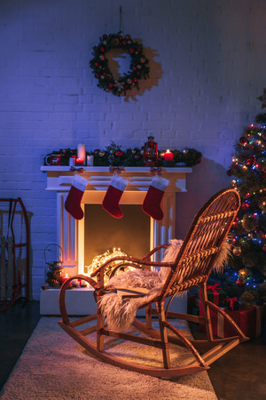 Fireplace with Christmas decorations near Christmas tree and wooden rocking chair Stock Photo