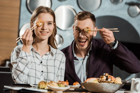 Lovely couple having fun while eating sushi rolls in restaurant Stockfoto