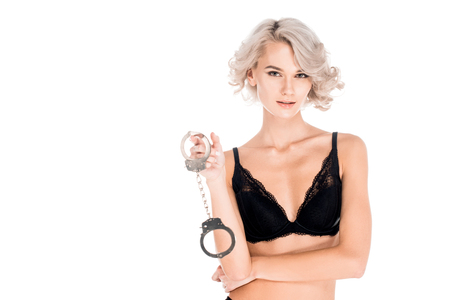 Wonderful blonde young adult woman in lingerie holding handcuffs isolated on white Stock Photo