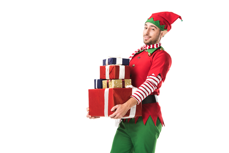 man in christmas elf costume looking at camera and carrying pile of presents isolated on white