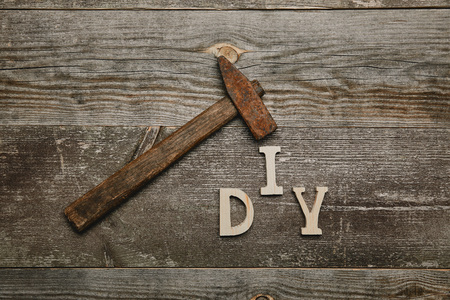 Top view of rusty hammer and diy sgn on wooden background