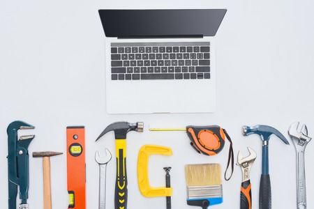 top view of laptop with various instruments lying on white Stock Photo
