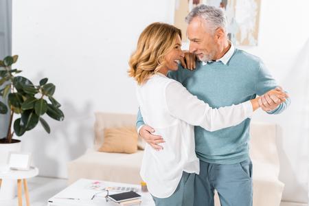 Paar, das sich beim Tanzen im Wohnzimmer zu Hause ansieht Standard-Bild