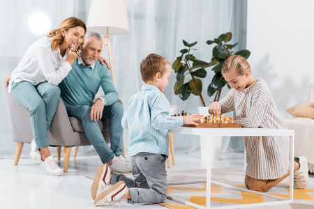 smiling kids playing chess while their grandparents sitting near at home