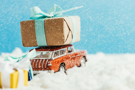 close-up shot of toy van with christmas gifts riding on snow on blue background