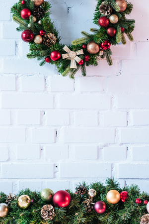 Christmas wreath with christmas balls on the background of white brick wall