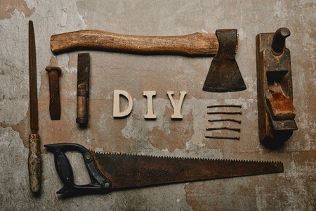 Flat lay with set of carpentry tools and diy sign on old surface Stock Photo