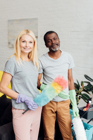 smiling blonde woman and african american man in rubber gloves holding dusters Stock Photo