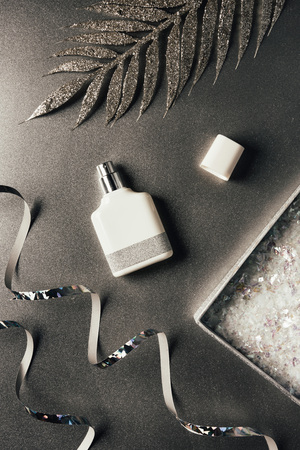 top view of perfume bottle, silver ribbons and shiny decorative leaves on grey 免版税图像