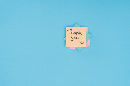colorful sticky notes with thank you lettering isolated on blue background