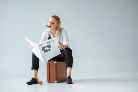 fashionable girl with cigar and glass of whiskey reading business newspaper while sitting on retro suitcase on grey