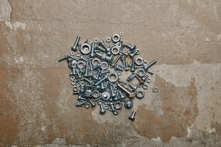 Top view of screws and bolts arranged on the background of old  surface