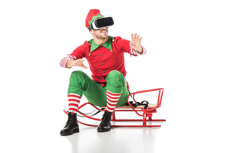 man in christmas elf costume sitting on sleigh and wearing virtual reality headset isolated on white