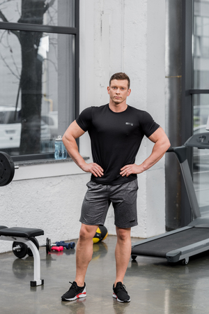 handsome muscular bodybuilder looking at camera in gym
