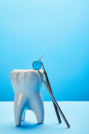 close up view of tooth model, dental mirror and probe on blue backdrop 写真素材 - 112161328