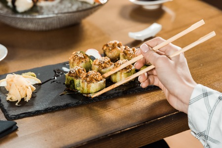 Cropped view of woman holding sushi with chopsticks in restaurant Stockfoto