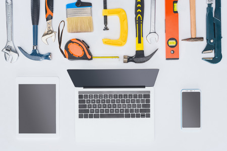 top view of laptop with various tools lying on white Stock Photo