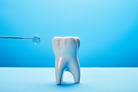 close up view of tooth model and dental mouth mirror on blue backdrop 写真素材 - 112162137