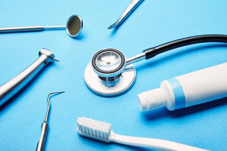 close up view of arrangement of sterile dental instruments, stethoscope, toothbrush and toothpaste on blue backdrop, dental care concept Stock Photo